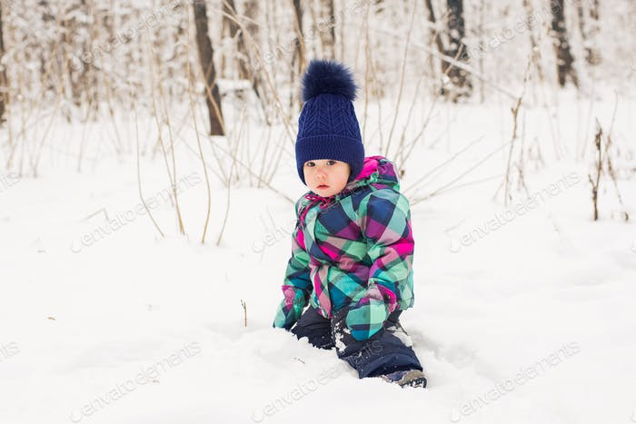 Toddler child playing in a snow in winter.