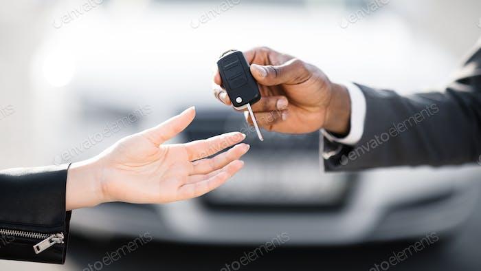 Verkauf von Autos. Händler geben Schlüssel an neuen Besitzer
