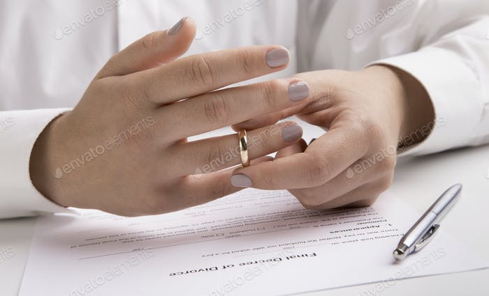 Close up view of hand taking off engagement ring