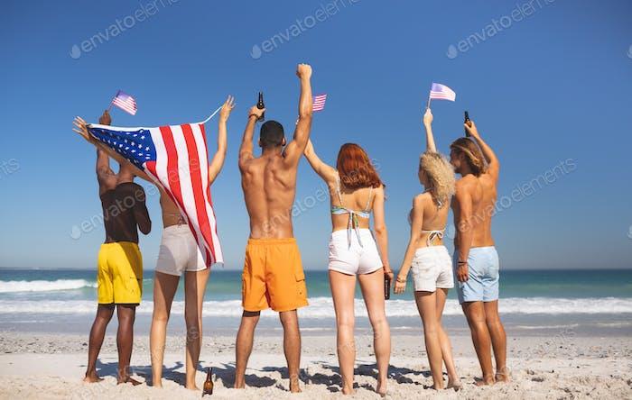 Rückansicht von verschiedenen Freunden heben ihre Hände am Strand, während halten amerikanische Flagge