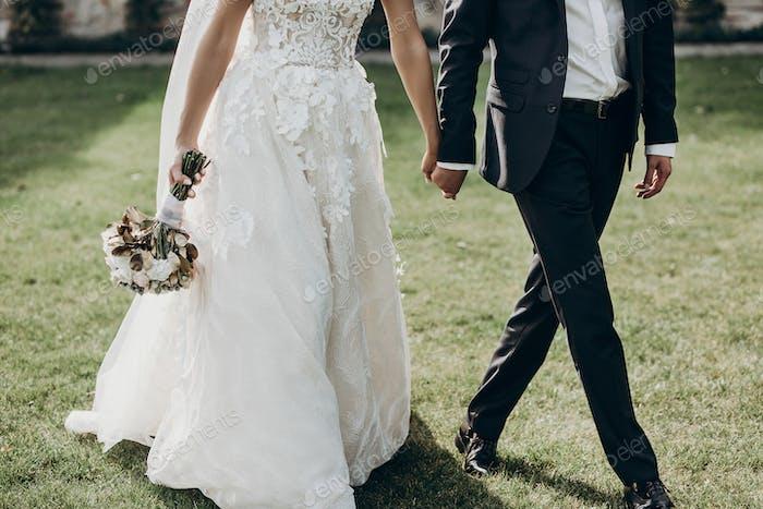 luxury wedding couple holding hands and walking
