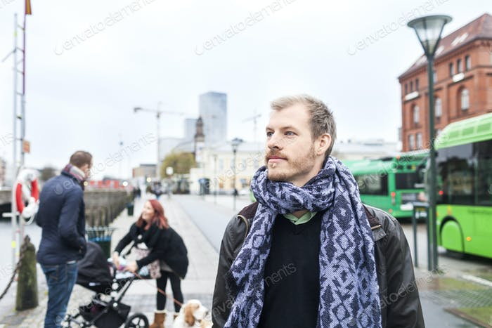 Thoughtful man on city sidewalk with family in background