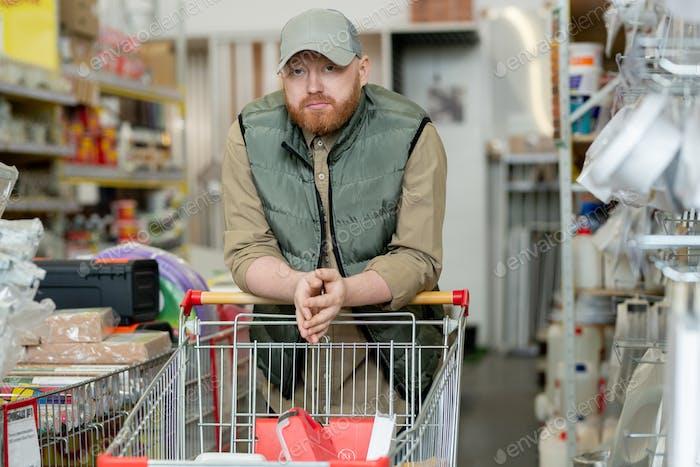 Bearded man in casualwear standing in hardware supermarket