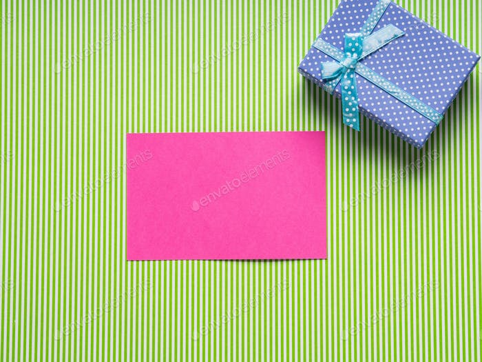Pink card and gift box on green