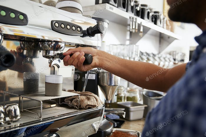 Young male barista preparing espresso at a cafe, close up