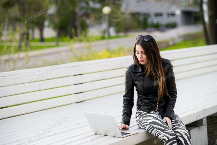 Girl works with laptop computer sitting on a bench in the park looking to camera and smiling