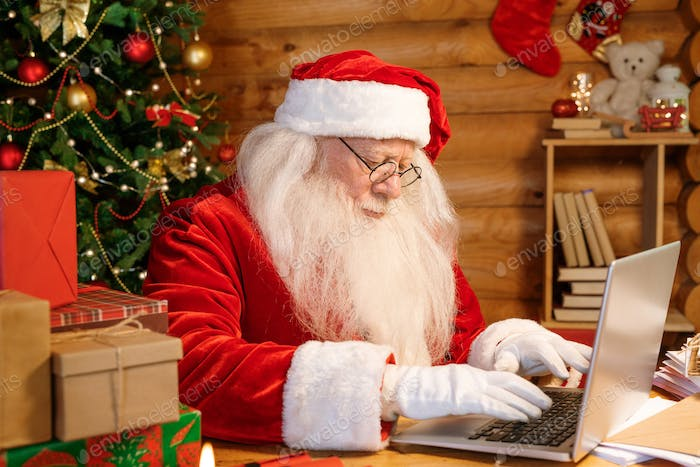 Serious Santa concentrating on answering electronic letters by laptop