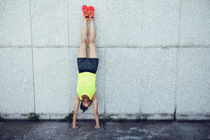 Woman doing a handstand leaning against wall