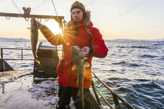 Joven pescador en el barco con dos Pescado grandes