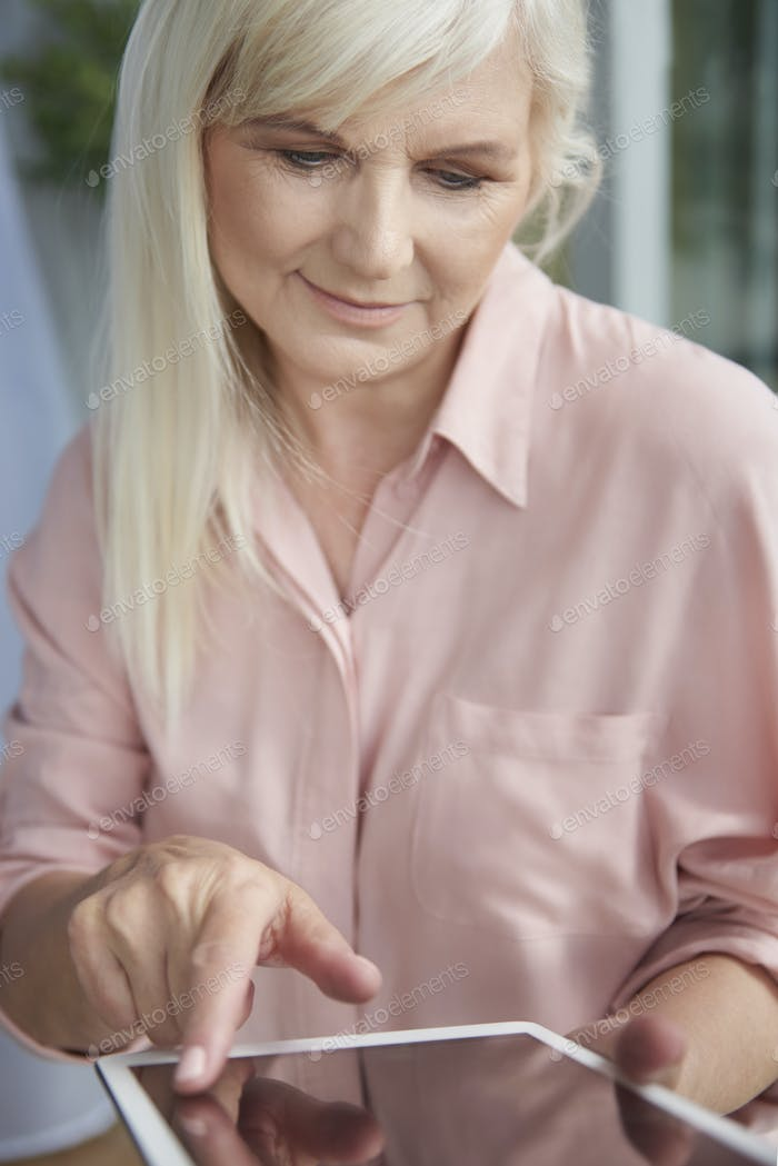 Mature woman using her digital tablet