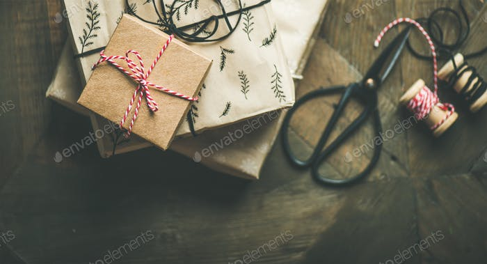 Flat-lay of holiday gift boxes, rope, scissors, copy space
