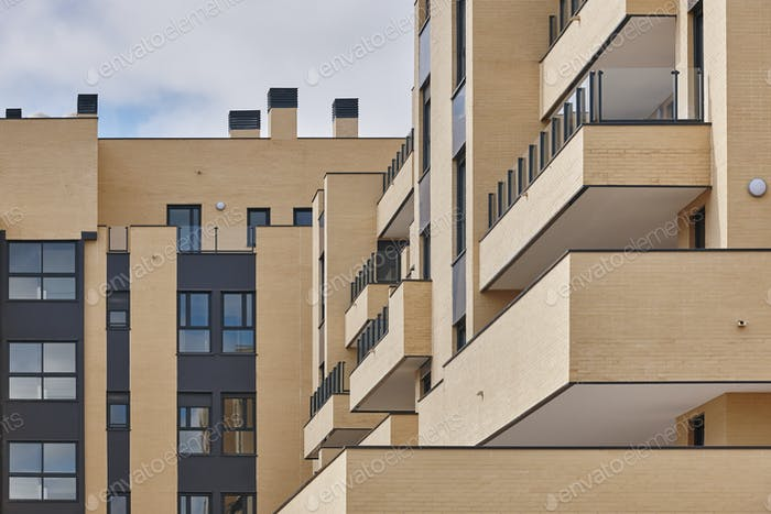 New brick building exterior facade with terraces. Construction. Buy, rent