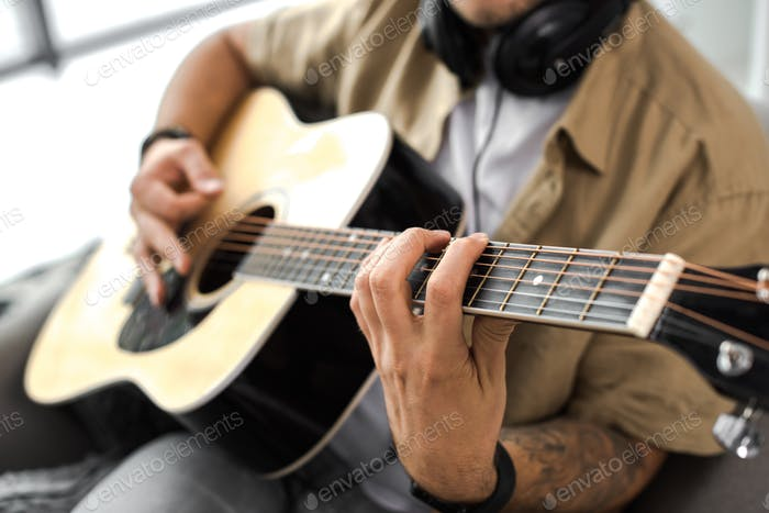 cropped shot of man playing acoustic guitar