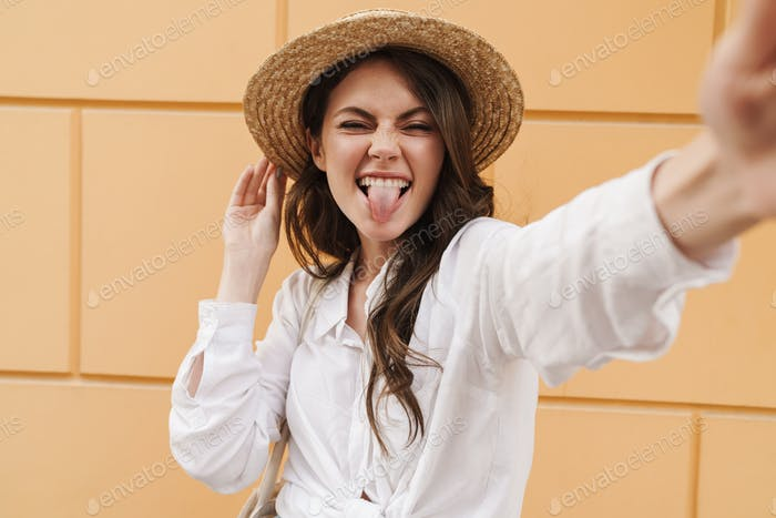 Portrait of young amusing woman grimacing and taking selfie photo