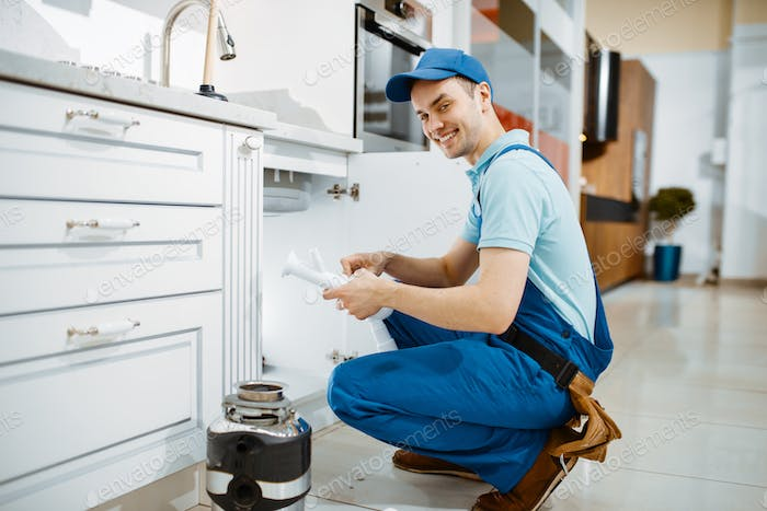 Smiling male plumber in uniform holds drain pipe