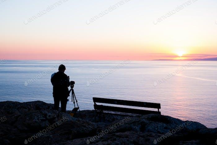 man photographer taking photos of sunset at the sea