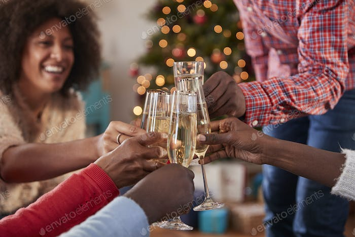 Close Up Of Friends Making A Toast With Champagne As They Celebrate Christmas At Home Together