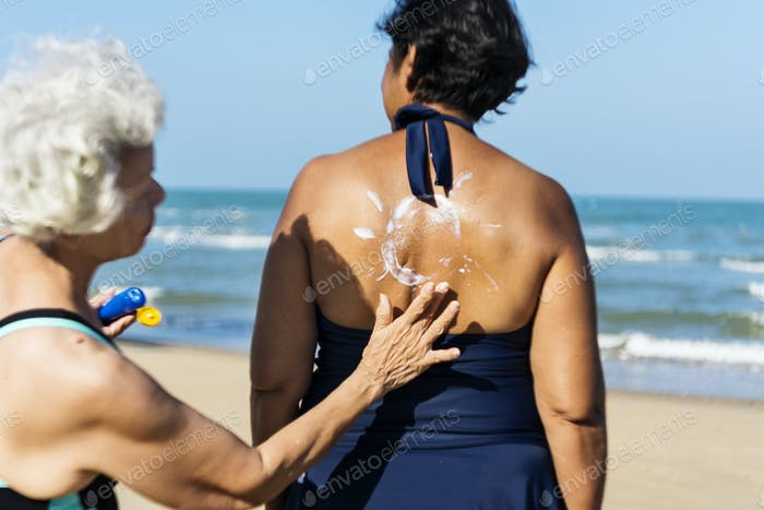 Woman helping to put on sunscreen