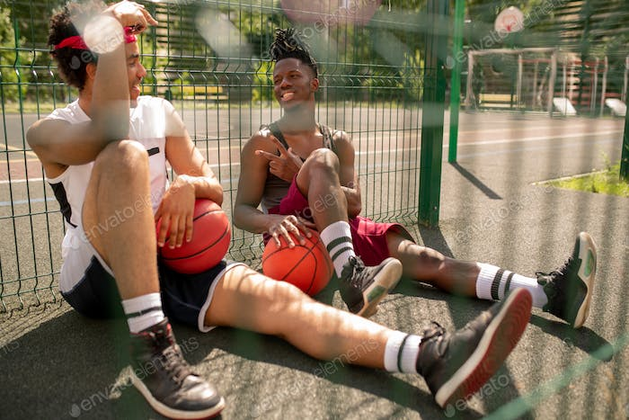 Two intercultural guys in activewear having rest on basketball court