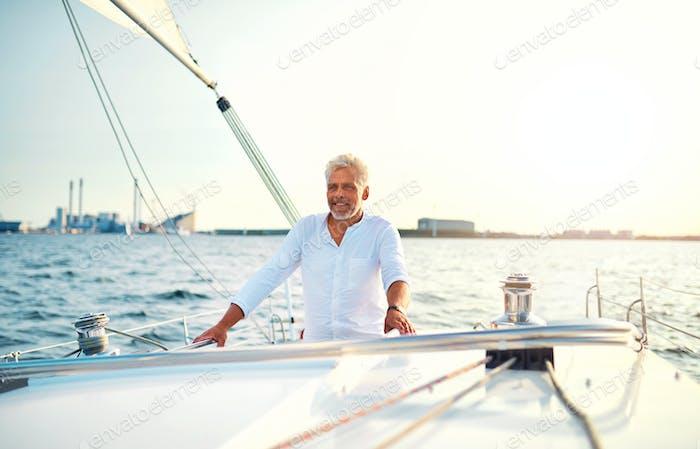 Reifer Mann stehend auf dem Deck seines Segelbootes
