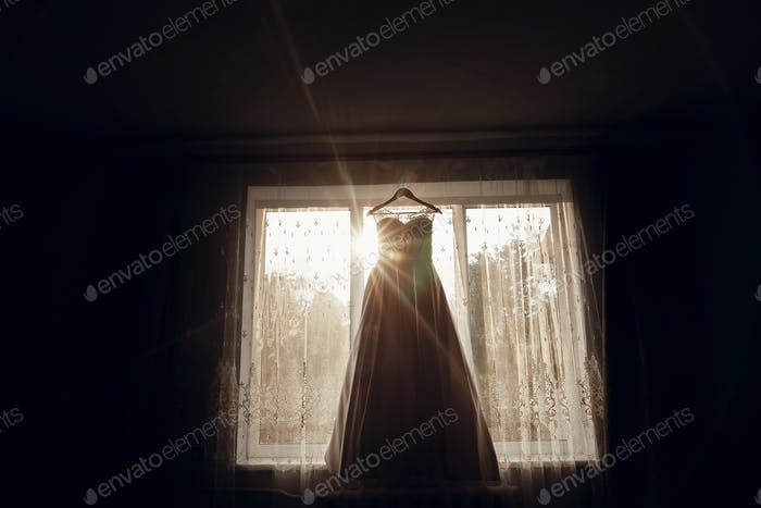 beautiful wedding dress hanging on hanger on window in morning light.