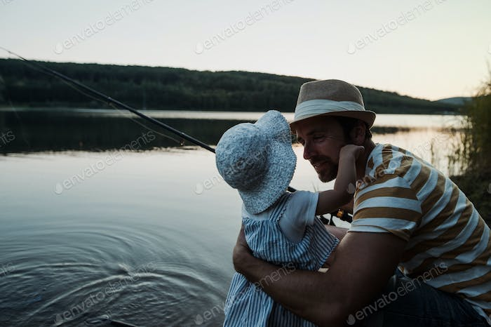 A mature father with a small toddler daughter outdoors fishing by a lake.