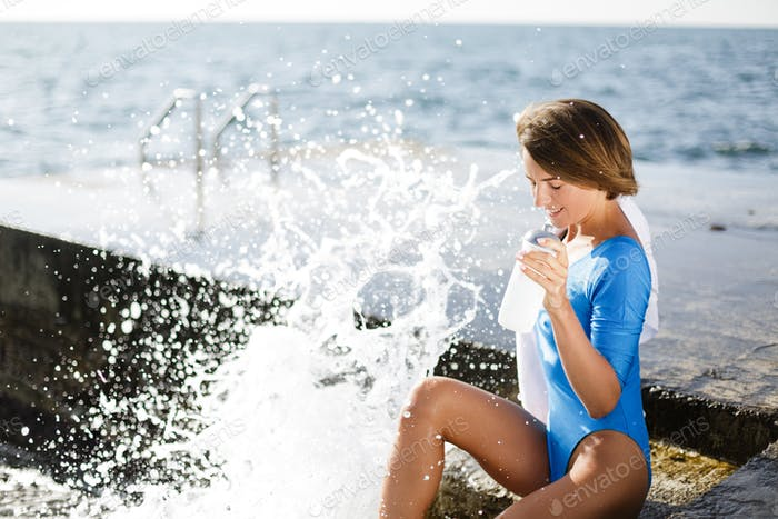 Schöne Dame im blauen Badeanzug sitzend und Trinkwasser mit Meerblick auf dem Hintergrund