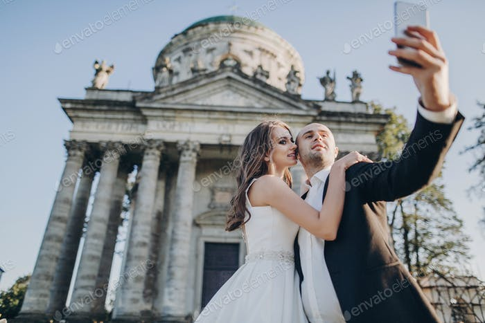Gorgeous bride and groom taking selfie on background of old castle in park