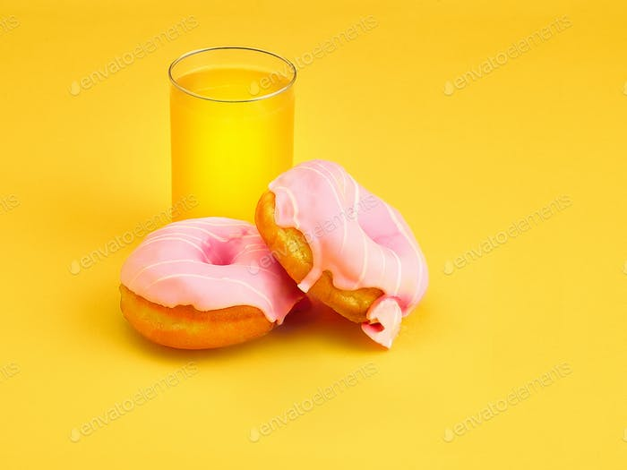 The donuts and fresh orange juice on yellow background