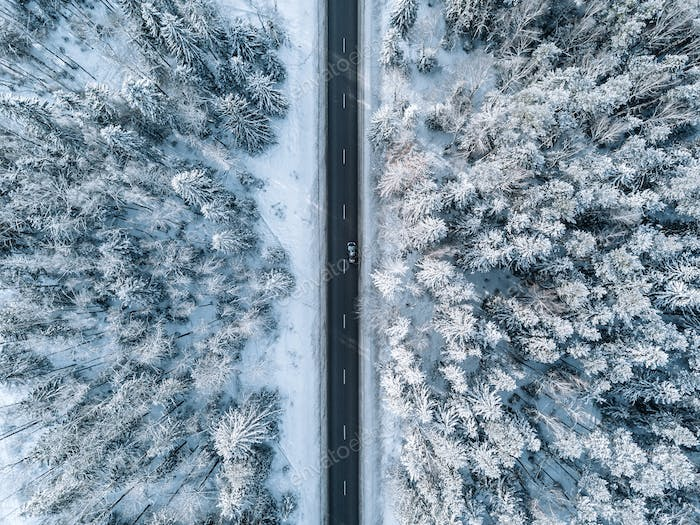Aerial view of winter road and forest with snow covered trees in Finland