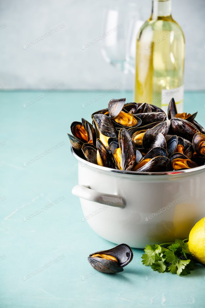 Pot of steamed mussels with lemon, herbs and white wine on blue background
