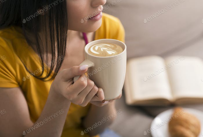 Closeup of millennial girl with cup of fresh coffee spending lazy time at home, copy space