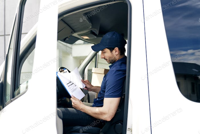 Courier sitting in the car and looking at documents