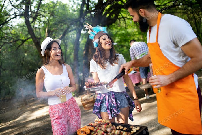 Group of happy friends having outdoor barbecue party and fun together