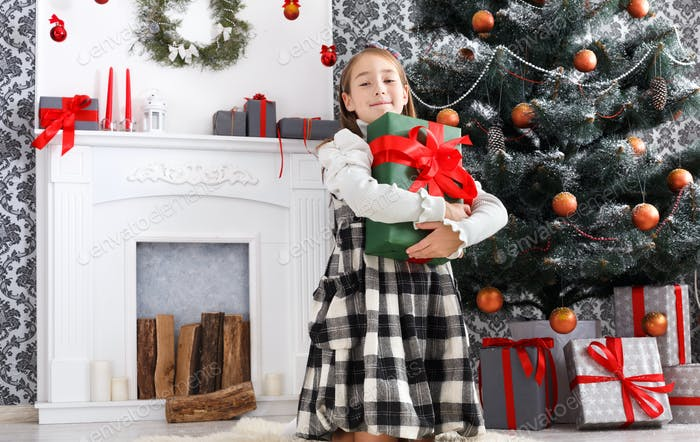 Beautiful child girl and christmas present indoors