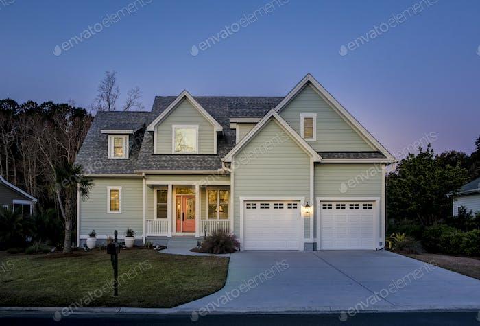 Vordere Erhebung eines schönen Hauses beleuchtet in der Dämmerung.