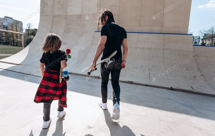 Father and his little son dressed in the stylish casual clothes walk with the skateboards in their