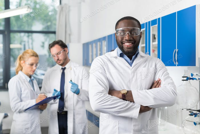 Happy Smiling African American Scientist Stand In Front Of Colleagues In Laboratory Making Notes Of
