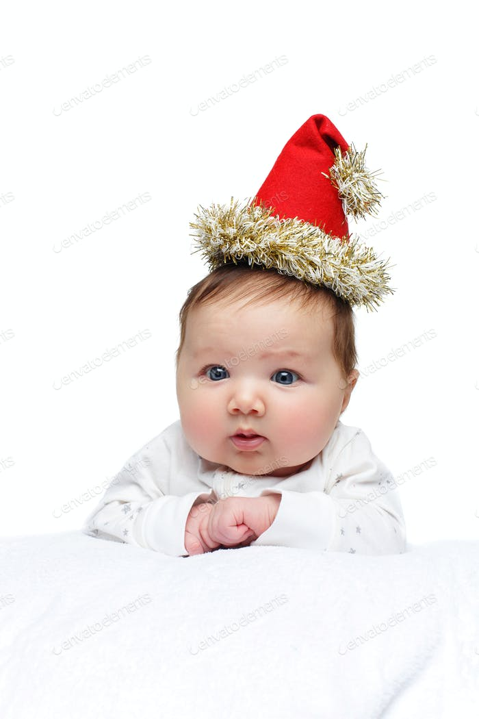 beautiful baby girl in christmas hat on white blanket