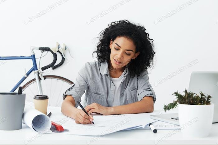 Lächelnde junge dunkelhäutige Selbständige Architektin mit Afro-Frisur macht Zeichnung an ihr h