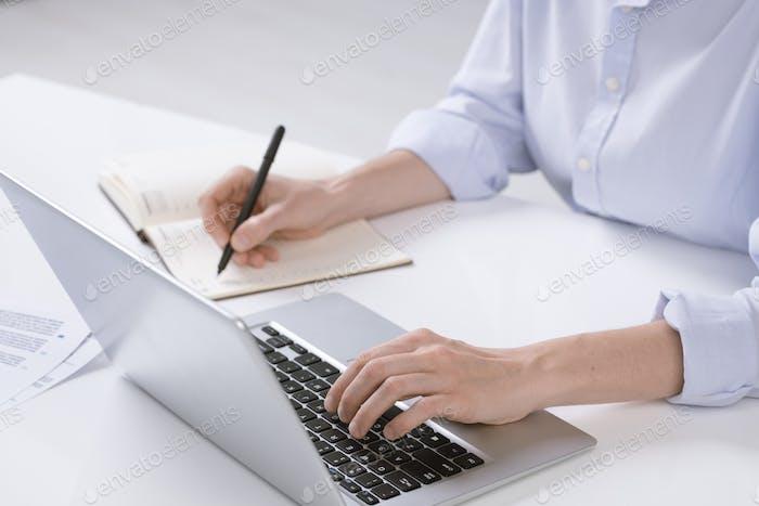 Hand der jungen Geschäftsfrau drücken Tasten der Laptop-Tastatur während der Notizen