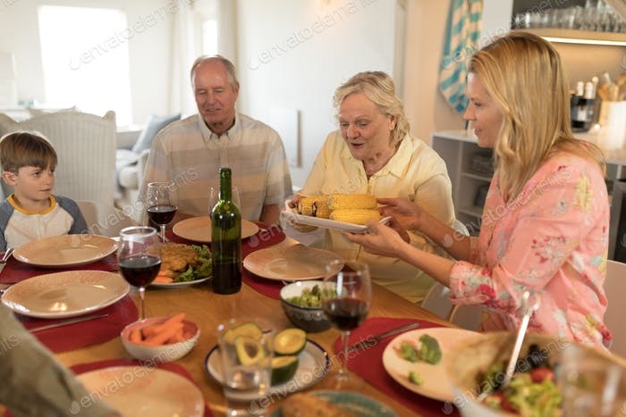 Side view of a multi-generation family having meal on dining table at home