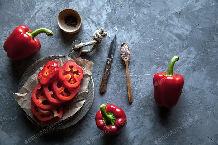 Geschnittene Paprika auf einem Schneidebrett mit einem Messer und reifen Pfeffer