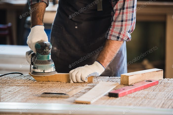 Worker grinds the wood of angular grinding machine