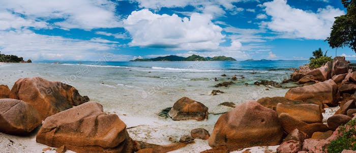 Tropical rockbound panorama landscape with white fluffy clouds above Praslin island. Anse Severe