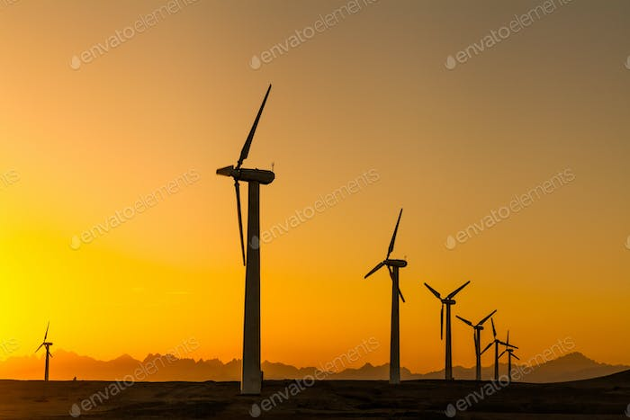 Large wind turbines in the desert against mountains