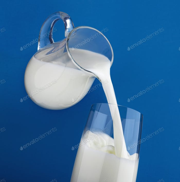 Pouring milk in glass with splash isolated on blue background