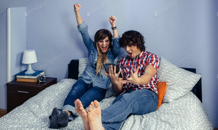 Couple celebrating victory watching sport