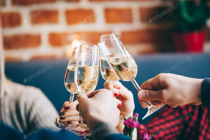 Four glasses of champagne in a toast