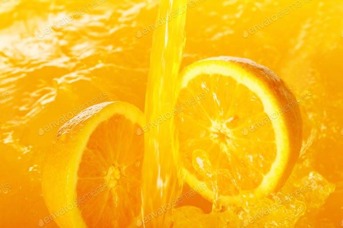 Fresh oranges falling in juice